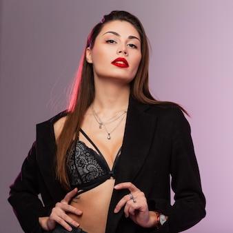 Glamouröses porträt junge schöne frau mit sexy roten lippen mit langen schicken braunen haaren in spitzenunterwäsche in stilvollem schwarzem mantel im studio mit hellem licht. ziemlich herrliches sinnliches mädchenmodell.