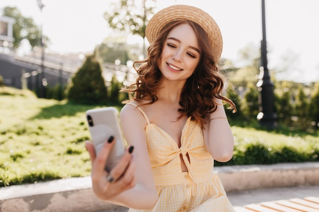 Glamouröses rothaariges mädchen, das telefon für selfie benutzt. außenaufnahme der atemberaubenden eleganten dame in der gelben kleidung, die im park kühlt.