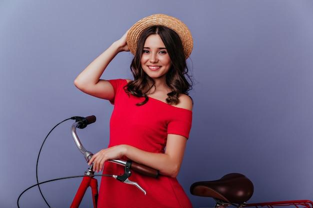 Glamouröses scherzhaftes mädchen im sommerhut, der auf fahrrad sitzt. erstaunliche weiße frau, die auf fahrrad mit lila innenraum aufwirft.