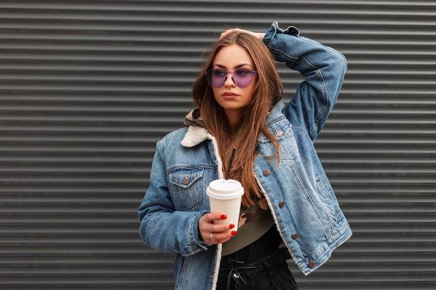 Glamouröses urbanes junges frauenmodell in trendiger lila brille in stylischer jeansjacke mit tasse heißem getränk, das draußen in der nähe einer metallwand posiert. attraktives hipster-mädchen mit kaffee genießt den frühlingstag