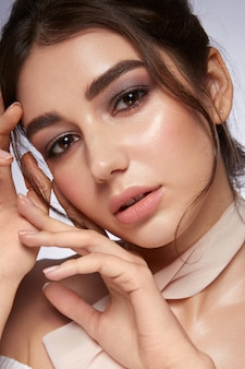 Glamourporträt des schönen frauenmodells mit frischem täglichen make-up und romantischer frisur. modisch glänzender textmarker auf der haut, sexy, glänzendes lippen-make-up und dunkle augenbrauen