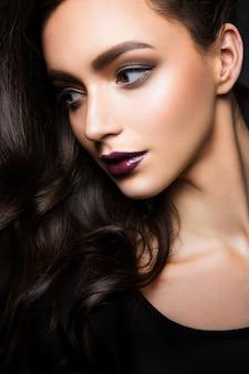 Glamourporträt des schönen frauenmodells mit frischem täglichen make-up und romantischer gewellter frisur