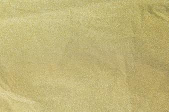 Glänzendes Papier des goldenen Funkelns wird für Weihnachtshintergrund, Feierkonzept zerknittert.