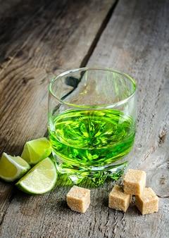 Glas absinth mit limetten- und zuckerwürfeln