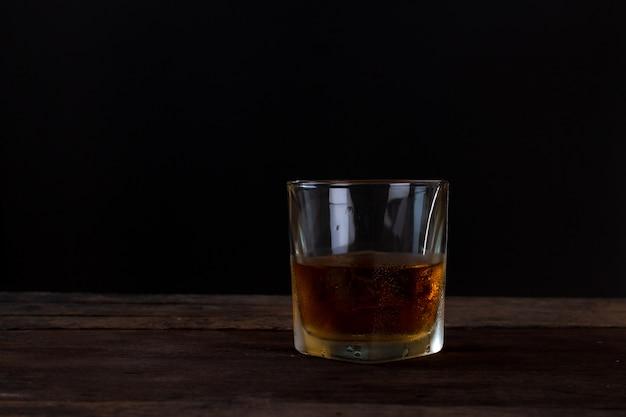 Glas alkohol scotch whisky mit eis auf holztisch und schwarzem hintergrund