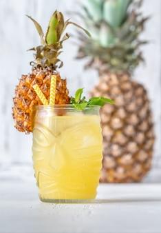 Glas ananas-tiki-art-cocktail auf weißem hintergrund