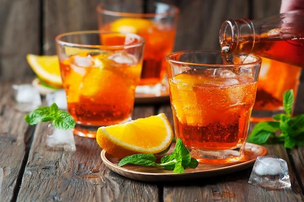 Glas aperol mit eis, orange und minze