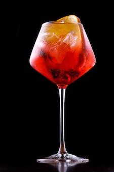 Glas aperol-spritz-cocktail auf einem schwarzen hintergrund schließen oben