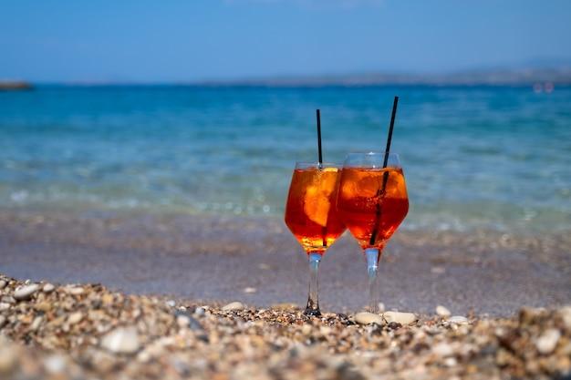 Glas aperol spritz cocktail steht auf sand am meer