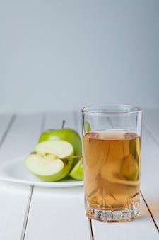 Glas apfelsaft und äpfel auf holztisch, auf naturhintergrund