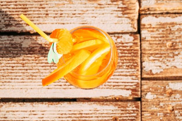 Glas appetitanregendes orangensaftgetränk mit kalk auf holzoberfläche