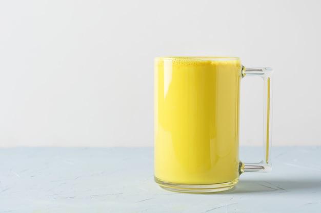 Glas ayurvedische goldene gelbwurz latte-milch mit kurkumaonweiß.