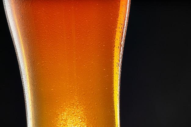 Glas bier auf schwarzem hintergrund, kopienraum