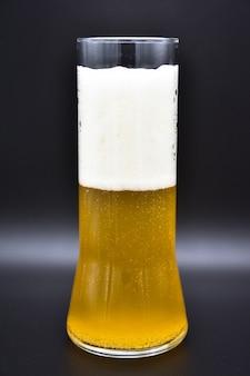 Glas bier auf schwarzem hintergrund