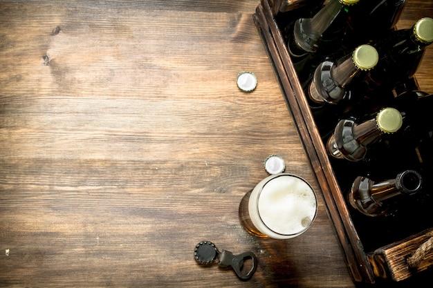 Glas bier mit einer schachtel und einem flaschenöffner. auf einem holztisch.