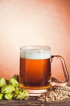Glas bier mit hopfen und gerste auf dem holztisch