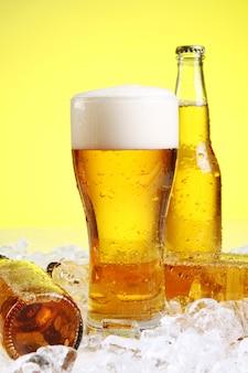 Glas bier mit schaum auf gelbem grund
