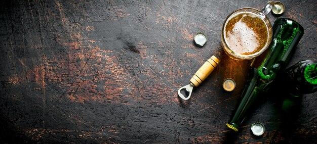 Glas bier und eine flasche. auf dunklem rustikalem tisch