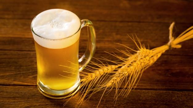 Glas bier und gerstenreis auf holztisch im goldenen licht.