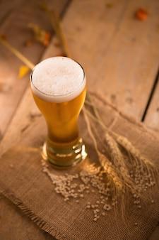 Glas bier und gerstenreis auf holztisch im goldenen licht