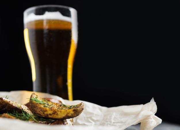 Glas bier- und landhausstilkartoffeln mit dill auf dunklem hintergrund