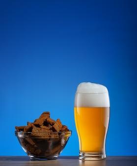 Glas bier- und roggencracker in der platte auf blauem hintergrund