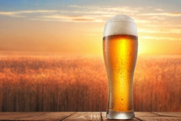 Glas bier vor dem hintergrund eines weizenfeldes