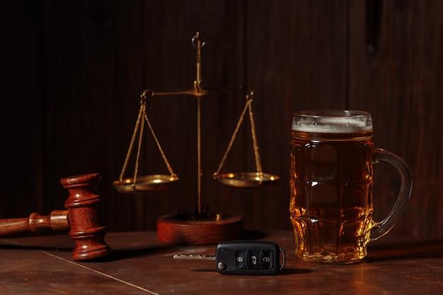 Glas bierautoschlüssel und hölzerner richterhammer in einem notar-alkohol- und gesetzeskonzept