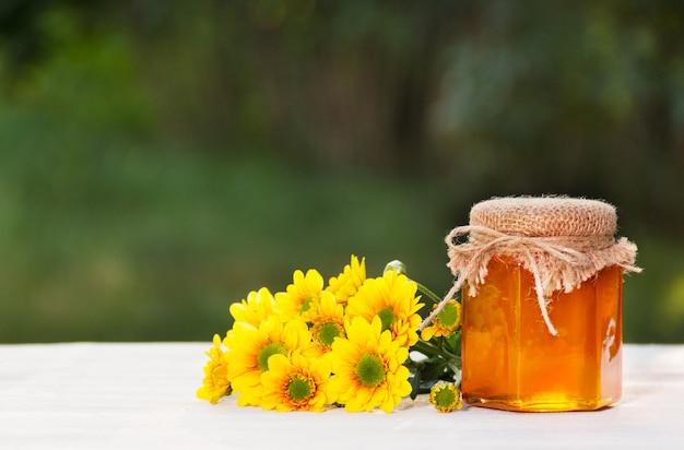 Glas blumenhonig und gelbe blüten