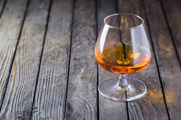 Glas brandy oder cognac und flasche im dunkeln.