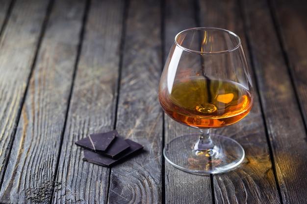 Glas brandy oder cognac und schokolade auf dunkel.