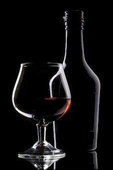 Glas brandy und flasche auf schwarzem hintergrund