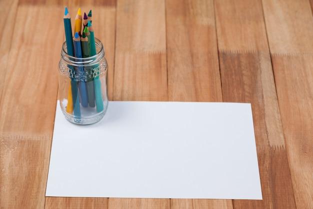 Glas buntstifte auf weißem papier