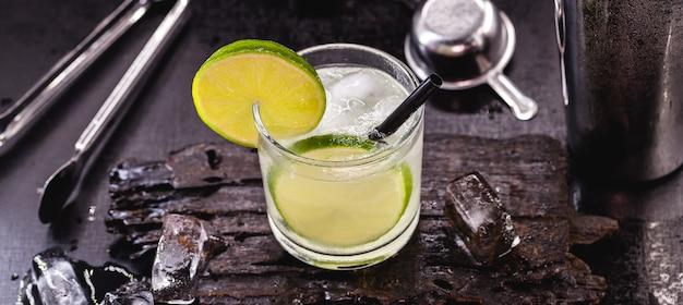 Glas caipirinha mit barutensilien. typisches getränk aus brasilien, hergestellt mit zitrone, auf einem schwarzen tisch
