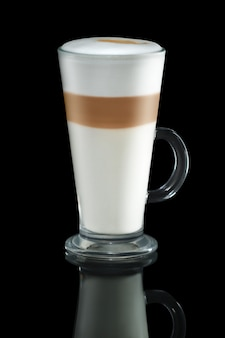 Glas cappuccino mit der reflexion getrennt auf schwarzem