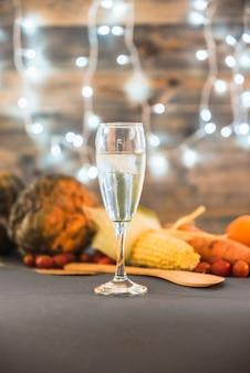 Glas champagner auf tabelle mit gemüse