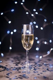 Glas champagner mit partydekoration nachts