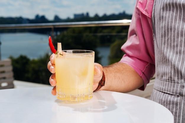 Glas cocktail. hübscher stilvoller mann, der einfaches rosa hemd hält, das glas des kalten cocktails hält