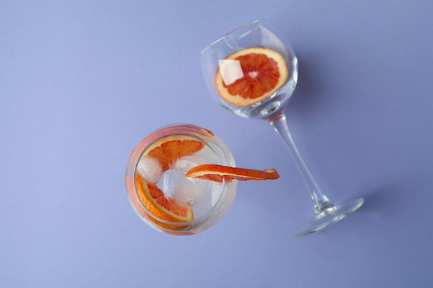 Glas cocktail mit grapefruit auf violettem hintergrund