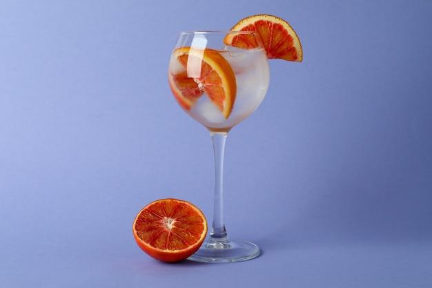 Glas cocktail mit grapefruit auf violetter oberfläche