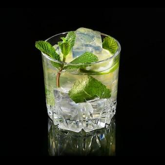 Glas cocktail mit rum, kalk, eiswürfeln und tadellosen blättern auf schwarzem spiegelhintergrund.