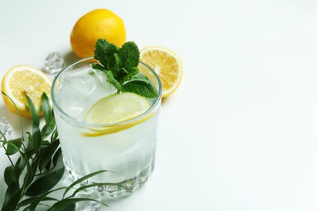 Glas cocktail mit zitrone auf weißer oberfläche
