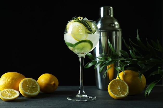 Glas cocktail mit zitrusfrüchten gegen dunkle oberfläche