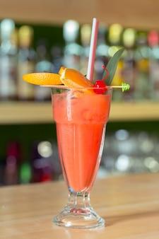 Glas cocktail verziert mit früchten am barzählerhintergrund
