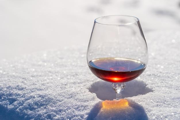 Glas cognac auf einem bett aus schnee und weißem hintergrund, nah oben. konzept des weihnachtswintermorgens