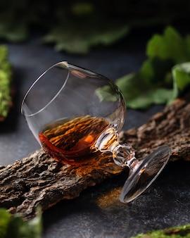 Glas cognac auf einer baumrinde mit eichenlaub