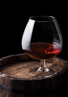 Glas cognac brandy getränk oben auf holzfass auf schwarzem hintergrund