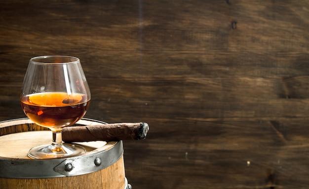 Glas cognac mit einer zigarre auf einem fass. auf einem hölzernen hintergrund.