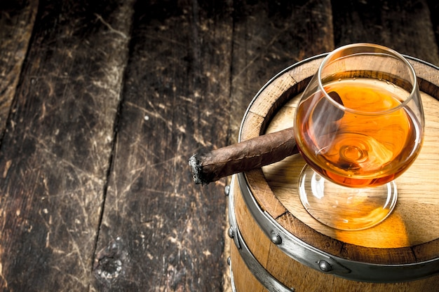 Glas cognac mit einer zigarre auf einem fass