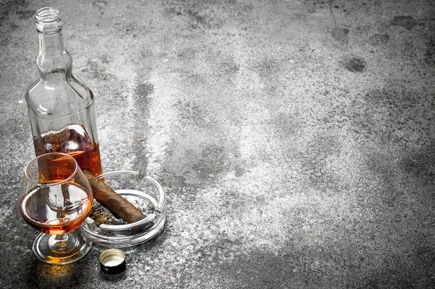 Glas cognac mit einer zigarre. auf einem rustikalen hintergrund.